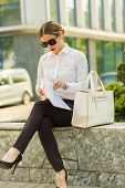 stock photo of shiting  - Stylish business woman in the city street - JPG