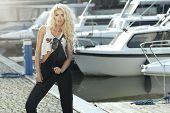 image of dungarees  - Stylish woman in dungarees standing on marina - JPG