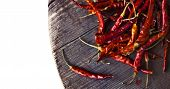 stock photo of pepper  - Red hot chili peppers on an old wooden table texture - JPG
