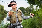 picture of fisherman  - Young fisherman on the river bank - JPG