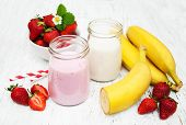 picture of yogurt  - Bananas and strawberries with yogurt on a wooden background - JPG