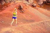 foto of canary  - Young happy woman running or power walking in mountains on sunny summer day. Beautiful natural landscape and female runner jogging exercising outdoors in nature rocky trail footpath on La Palma Canary Islands