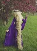 foto of crap  - Young woman dressed as Rapunzel wearing purple velvet medieval costume with long - JPG