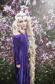 pic of magnolia  - Beautiful young woman dressed as Rapunzel wearing velvet purple medieval gown standing in front of blooming magnolia tree - JPG