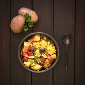 image of baked potato  - Baked potato eggplant zucchini and tomato casserole in rustic bowl raw potatoes parsley leaf and wooden spoon on the side photographed overhead on dark wood with natural light - JPG
