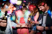 stock photo of flute  - Group of young friends with flutes of champagne having party in club - JPG
