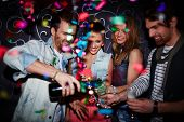 stock photo of flute  - Cool guy pouring champagne in flutes of his friends - JPG