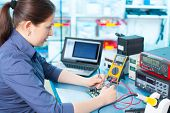image of circuits  - Woman with a tester and a printed circuit board - JPG
