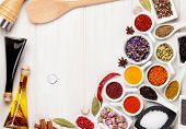 image of condiment  - Various spices and condiments on white wooden background - JPG