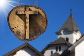 stock photo of mountain chain  - Wooden Christian cross on a section of tree trunk hanging from a metal chain - JPG