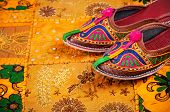 picture of shoes colorful  - Colorful ethnic shoes on yellow Rajasthan cushion cover on flea market in India - JPG