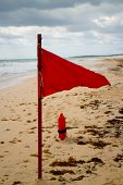 stock photo of lifeguard  - Red flag at the beach with torpedo lifeguard buoy - JPG