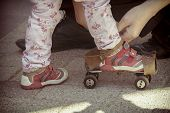 picture of roller-skating  - Father helping her little daughter to try on vintage roller skates - JPG