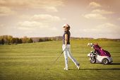 picture of golf bag  - Female golfer on fairway with golf club and bag with empty copyspace - JPG
