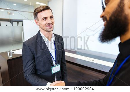 Happy handsome businessman shaking hands with young bearded african american colleague in office