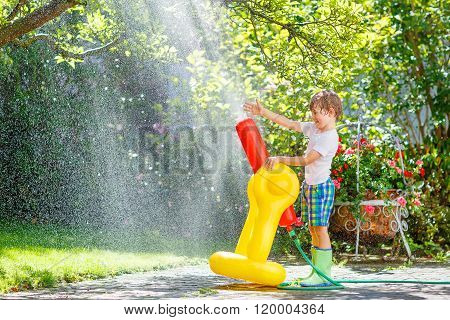 little kid boy  playing  with a garden hose