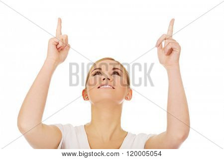 Happy young woman pointing up with both hands