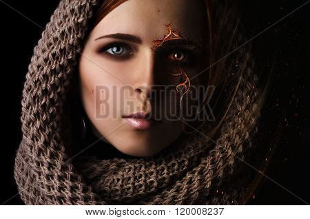 Fantasy processing portrait of a young girl with a burning pattern on the face in a scarf on a black