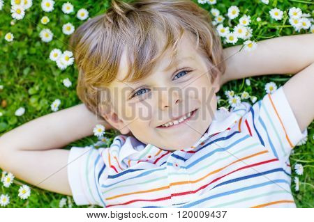 Happy kid boy laying on green grass in summer