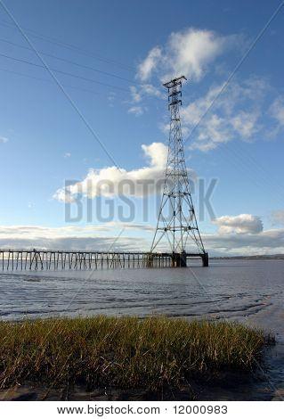 Tall pylon carrying cables over a tidal estuary