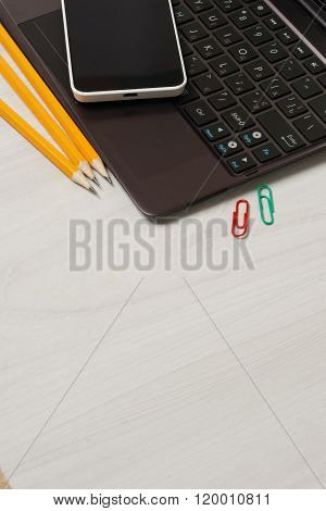 School or student supplies with closed slim notebook and smartphone on a white wooden table surface