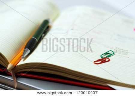 Pen and pencil on a open diary close-up. Business theme background