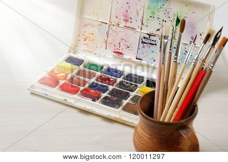 Bright watercolor paints and used brushes for painting on a wooden table surfase. Vintage toned phot