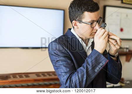 Jeweler examining diamond thoroughly through loupe jewel