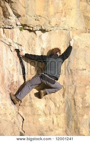Free Climber Traversing Rock Face