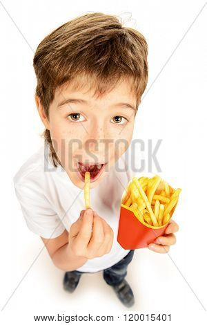 Happy nine year old boy eating french fries and smiling. Fast food. Concept of healthy and unhealthy food. Isolated over white.