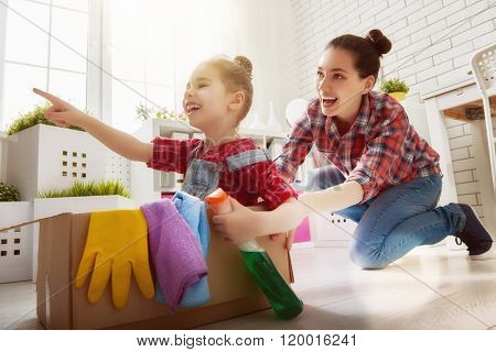 Happy family cleans the room. Mother and daughter do the cleaning in the house. A young woman and a little child girl having fun and riding in cardboard boxes at home.