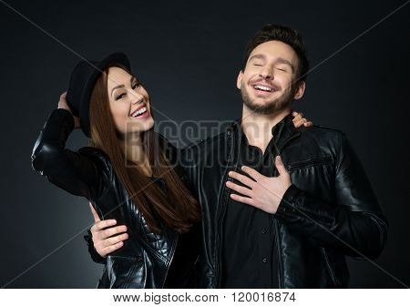 Cheerful smiling couple standing isolated on black background