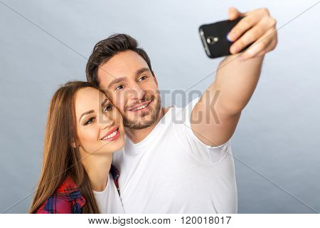 Pleasant young couple making selfie