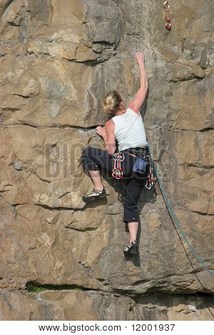 Female Climber ascending cliff face