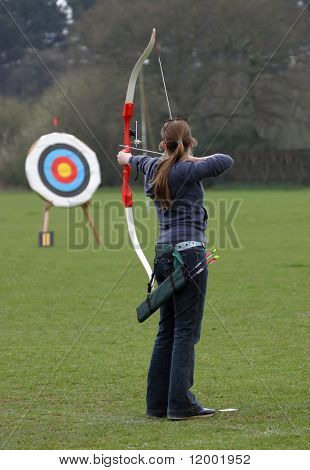 Female archer aiming at target