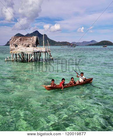 Bajau Laut kids paddling a boat