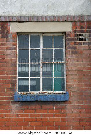 Rusting metal-framed window in old building