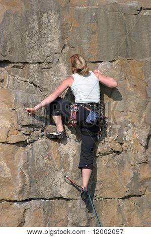 Female climber ascending sheer cliff face
