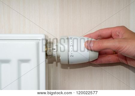Woman Hand Adjusting The Temperature By Thermostat