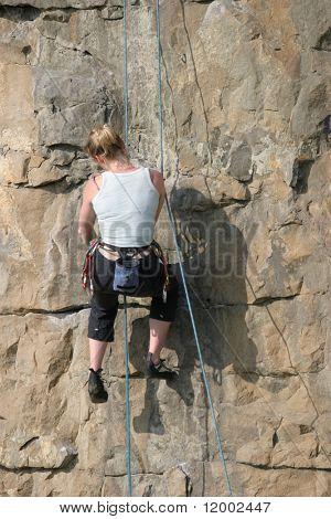 Blonde climber adjusting equipment
