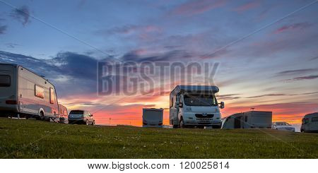 Caravans and cars parked on a grassy campground in summer under beautiful sunset