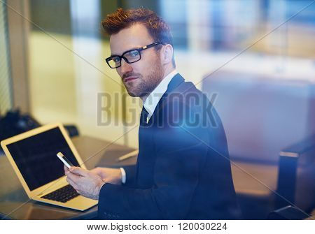 Elegant manager with cellphone and laptop planning work
