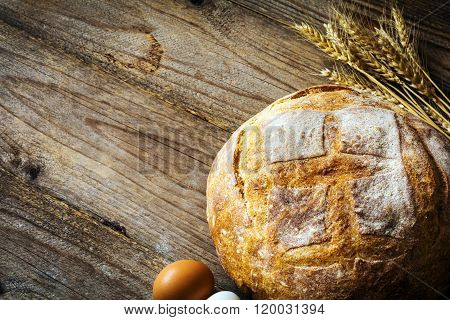 Food background: Loaf of fresh bread, golden wheat ears and fresh eggs on wooden background, copy space