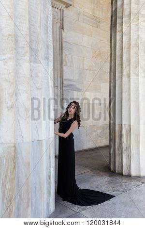 young lady in black dress near column