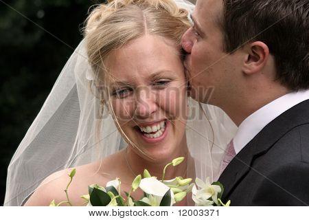 Bridegroom kissing his wife