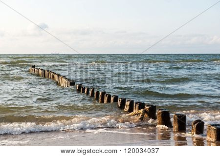 Breakwater Of One Row Of Wooden Poles At The Sea Coast