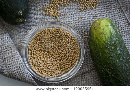 Mustard seeds and a cucumber. Ingredients for pickles