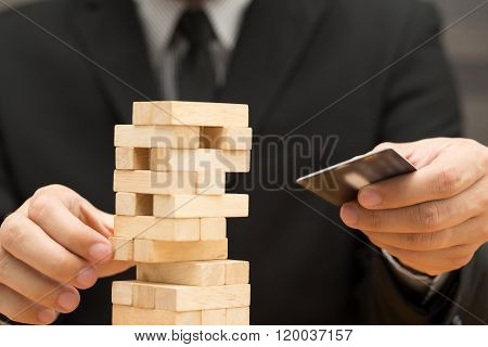 Risk Of Credit Card Concept. Businessman Choosing The Wood Block And Holding Credit Card