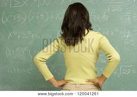 Female student stood in front of blackboard