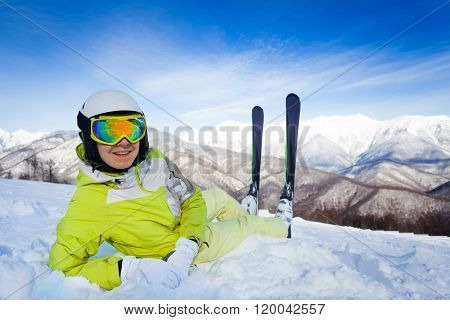 Skier woman lay in snow with ski and turn back